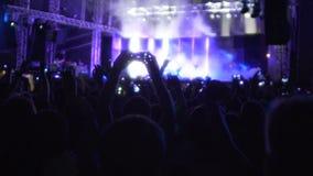跳跃和举他们的手的愉快的观众宣扬在摇滚小组音乐会 影视素材
