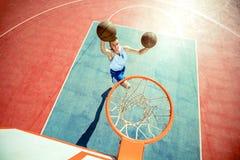 跳跃和做意想不到的灌篮的年轻人演奏streetball,篮球 都市地道 免版税图库摄影