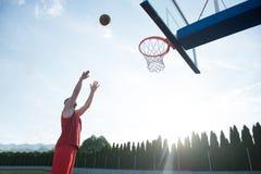 跳跃和做意想不到的灌篮的年轻人演奏stree 库存照片