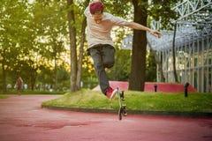 跳跃和做把戏的年轻男性滑板车手 免版税库存图片