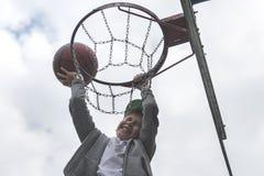 跳跃和做目标的一个小男孩演奏streetball,篮球 投掷在圆环的篮球球 体育的概念 免版税图库摄影