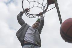 跳跃和做目标的一个小男孩演奏streetball,篮球 投掷在圆环的篮球球 体育的概念 免版税库存图片