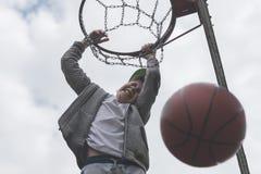 跳跃和做目标的一个小男孩演奏streetball,篮球 投掷在圆环的篮球球 体育的概念 图库摄影