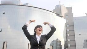 跳跃和庆祝在办公楼前面的愉快的白种人女商人 影视素材