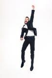 跳跃和庆祝成功的愉快的激动的英俊的年轻商人 库存图片