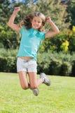 跳跃和微笑对照相机的逗人喜爱的女孩 免版税库存图片