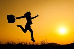 跳跃和拿着袋子日落剪影的女商人 库存照片