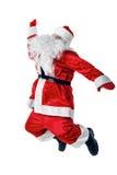 跳跃和挥动他的胳膊的快乐的圣诞老人 免版税库存照片