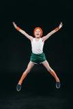 跳跃和看照相机的运动服的愉快的男孩 免版税库存图片