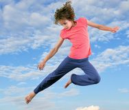 跳跃和跳舞反对蓝色多云天空的小女孩 免版税库存照片