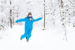 跳跃在一个多雪的公园的滑稽的男孩 免版税图库摄影