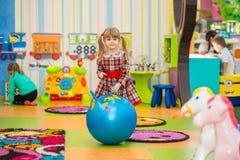 跳跃在一个大橡胶球的愉快的微笑的小女孩 免版税图库摄影
