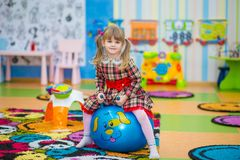 跳跃在一个大橡胶球的愉快的微笑的小女孩 免版税库存照片