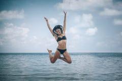 跳跃在一个热带海滩的两个愉快的女孩 免版税库存图片