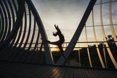 跳跃在一座概念性桥梁的妇女的形状 库存照片