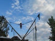 跳跃在与女孩的一个狂欢节的橡皮筋上流反对多云天空 图库摄影