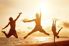 跳跃在与日落的海滩的青年人 免版税库存图片