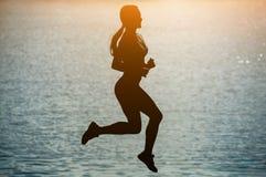 跳跃在体育期间的一名美丽,运动妇女的剪影在河附近在日落 免版税库存照片