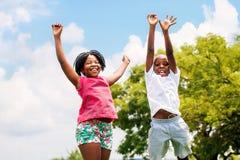 跳跃在公园的两个非洲孩子 免版税库存照片