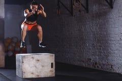 跳跃在十字架适合的健身房的妇女箱子 做箱子的运动员跳锻炼在健身房 库存照片