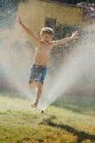 跳跃在喷水隆头的野生男孩 免版税库存图片