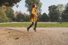 跳跃在城市公园的红头发人女孩 免版税库存图片