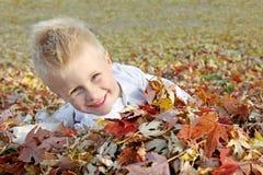 跳跃在堆的愉快的幼儿秋天叶子 免版税图库摄影