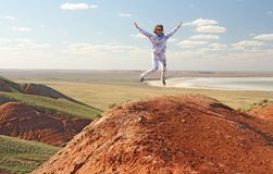 跳跃在夏天的女孩在山顶部,户外 喜悦 免版税库存照片