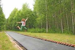 跳跃在夏天的女孩户外,在绷床 喜悦, 免版税库存照片