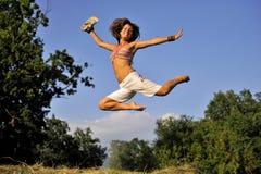 跳跃在夏时的愉快的妇女 库存照片