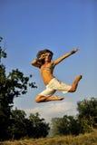 跳跃在夏时的愉快的妇女 免版税库存照片