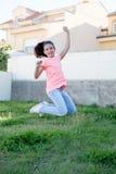 跳跃在外部的愉快的青春期前的女孩 免版税图库摄影