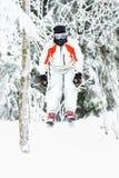 跳跃在多雪的倾斜的Freeride滑雪者 库存图片