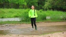 跳跃在大水池的愉快的女孩在公园 股票视频