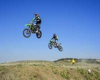 跳跃在天空中的两位竟赛者在motocros竞争时 库存照片