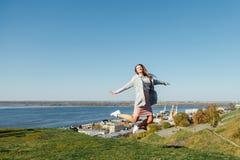 跳跃在天空中的愉快的妇女 免版税图库摄影