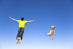 年轻跳跃在天空的人和狗 免版税库存照片