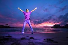 跳跃在威基基海滩,夏威夷的上流的紫色的年轻男孩 免版税图库摄影