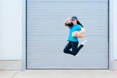 跳跃在存储仓前面的女性交付工作者 免版税库存图片