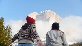 跳跃在山前面的两旅行的愉快的年轻女人 影视素材