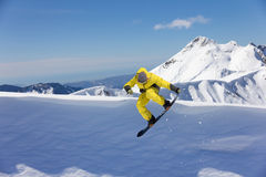 跳跃在山的雪板车手 极端雪板体育 免版税库存图片