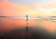 跳跃在巴厘岛的海滩的少妇在印度尼西亚 免版税库存图片