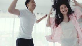 跳跃在床上的可爱的亚洲夫妇在卧室 股票录像