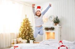 跳跃在床上的愉快的儿童女孩在圣诞节早晨 免版税库存照片