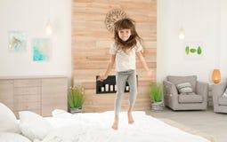 跳跃在床上的逗人喜爱的女孩 免版税库存照片