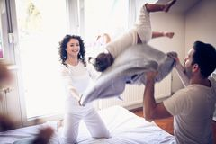 跳跃在床和枕头战上与妈妈和爸爸是乐趣 免版税库存照片