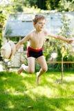 跳跃在庭院里的逗人喜爱的活跃孩子男孩在温暖的晴朗的夏日 看照相机的愉快的孩子 可爱的孩子与 库存照片