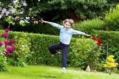 跳跃在庭院里的逗人喜爱的男孩 库存照片