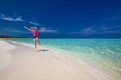 跳跃在异乎寻常的海滩,马尔代夫的桃红色上面的愉快的女孩 库存图片
