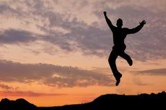 跳跃在日落的一个人的剪影 免版税库存照片
